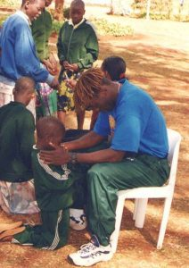 Henry praying with one of our orphans
